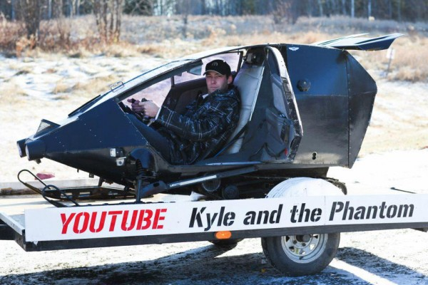 Kyle Anderson is pictured here with The Phantom, a fully enclosed snowmobile that he designed and built. The 26-year-old spent $1,500 manufacturing the machine with parts that he made or found. It has a heater, CD player, rearview TV monitor and an Indy 500 motor. Anderson is planning to take the snowmobile on a tour across the U.S. to generate investor interest in the mass production of his invention.