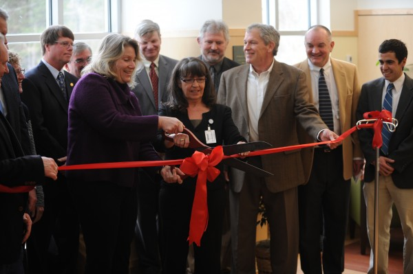 Rebecca Sargent (center, in purple), chairwoman of the board of trustees of Maine Coast Memorial Hospital, and Jayne Wixon (center, in black), nurse manager, cut a red ribbon to mark the opening of the Mary Dow Center for Cancer Care at Maine Coast Memorial Hospital in Ellsworth on Sunday.