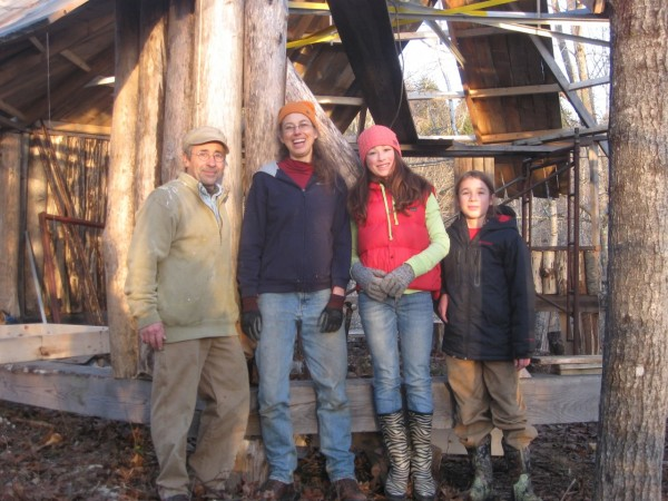 Paul Molyneaux (from left), poses with his wife Regina Grabrovac and their children, Oona and Asher Molyneaux, in front of the log cabin they are building behind their home in East Machias in fall 2012. The family is working on the project together to create a peaceful living space without electricity.