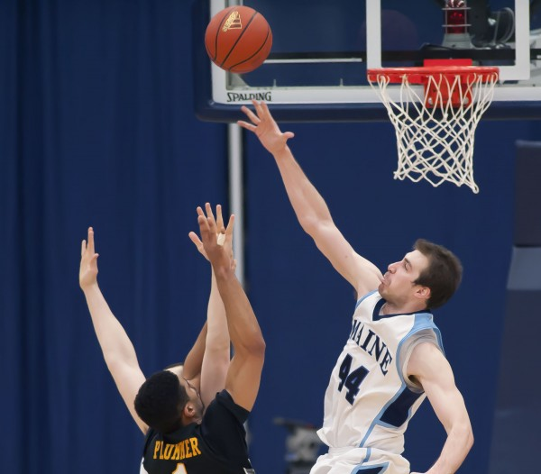 UMaine Men's basketball player Mike Allison (44) gets a hand in the face of UMBC player Chase Plummer (1) as he goes to the hoop in the second half of their game in Orono on Saturday, Jan. 5, 2013.