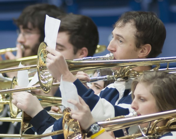 Mackenzie Bray keeps an eye and a hand on the music as he deftly plays the trombone as part of the Maine Screamin' Black Bear Pep Band on Saturday, Jan. 5, 2013, during the Maine UMBC basketball game in Orono.