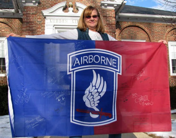 Librarian Peggy Malley displays the Army Airborne flag that the Ludden Memorial Library received Dec. 10.