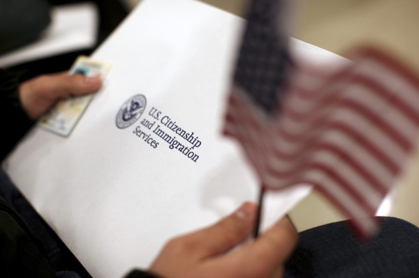A man holds an American flag while receiving his proof of U.S. citizenship during a ceremony in San Francisco, Calif., on Thursday, Jan. 30, 2013. President Barack Obama said on Wednesday that he believes it is possible to get an overhaul of the immigration system by the end of the year if not the first half of 2013.
