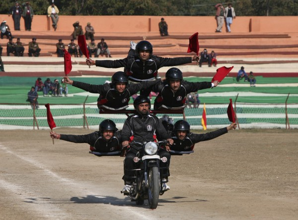 Indian policemen perform a stunt on a motorcycle during the Republic Day parade in Jammu on January 26, 2013. India celebrated its 64th Republic Day on Saturday.