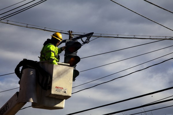 Doug Morin, systems and lighting technician for the city of Portland, removes a wind-damaged backing plate from a Commercial Street traffic signal Thursday, Jan. 31, 2013. Morin said he'd been busy since 7 a.m. repairing windblown signs and signals.
