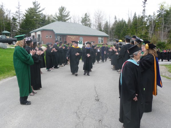 Graduating students at the University of Maine at Machias 100th graduation ceremony in 2011 stand and applaud their instructors as they head into the commencement ceremonies.