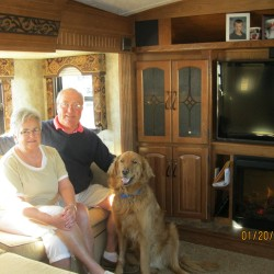 """Donna and George sit with their dog, Captain, in their """"rolling home,"""" a fifth wheel RV that hitches to the bed of their pickup truck."""