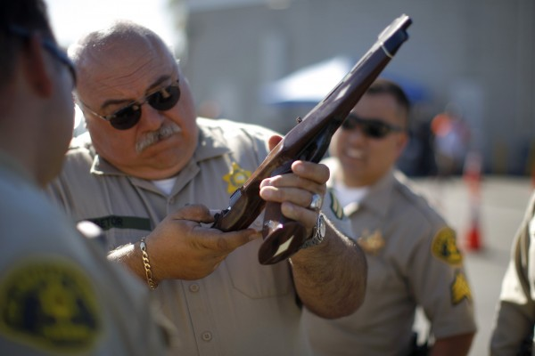 A Los Angeles County Sheriff's deputy takes in guns from motorists trading them in at the 'Gifts for Guns' gun buyback in Compton, California, January 21, 2013.