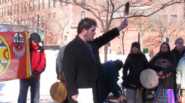 George Neptune, a member of the Passamaquoddy Tribe and educator at the Abbe Museum in Bar Harbor, hold up a feather after a speech on Saturday, Jan. 5, 2013, at an Idle No More rally in Portland. The rally was held to show solidarity with indigenous people worldwide.
