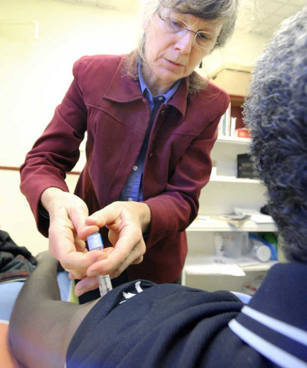 Dr. Alice Haines gives a free flu vaccine at the Trinity Jubilee Center in Lewiston.