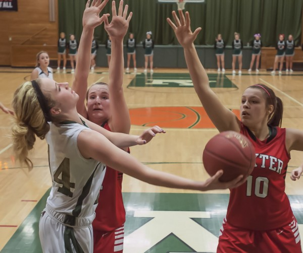 Penobscot Valley girls basketball player Sami Ireland (14) tries to loop a baseline shot under the arms of Dexter defenders Peyton Watson (24) and Abbie Melvin (10) in the fourth quarter of their game in Howland on Saturday afternoon. Dexter won 50-41.
