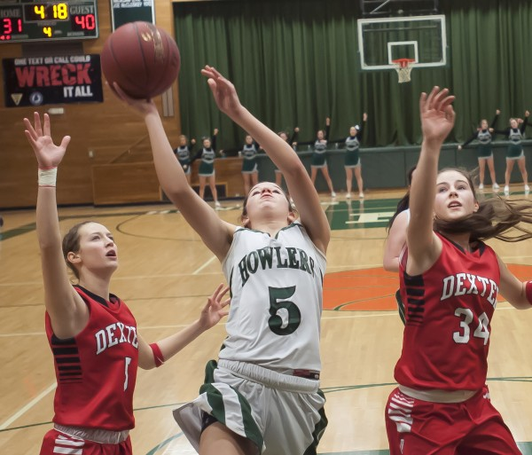 PVHS girls basketball player Amy Hallett (5) drives between Dexter's Jordyn Bell (5) and Michaela White (34) in the fourth quarter of their game Saturday in Howland. Dexter won 50-41.