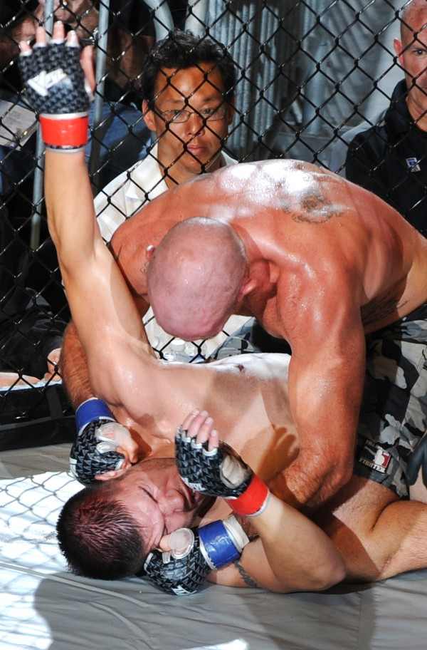 Jesse Peterson (top) lands a barrage of blows to the head of Cody Lightfoot during New England Fights Fight Night IV last September in Lewiston. Peterson won the title bout. NEF hosted five mixed martial arts cards between February and November 2012, averaging more than 2,500 fans per outing.