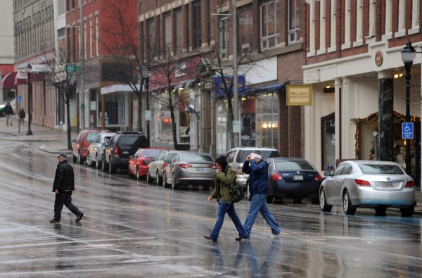 Pedestrians weather the storm on Thursday morning in downtown Bangor, with heavy wind gusts and rain swept over the region knocking down trees and causing power outages.
