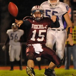 Foxcroft Academy quarterback Chris Shorey gets the ball away while being chased by John Bapst's Kurt Massey during a game in a game in October 2011. Massey is the defensive lineman recipient of the 2012 Frank J. Gaziano Lineman Awards.