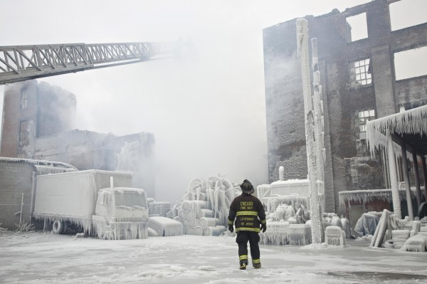 Chicago Fire Department Lt. Charley De Jesus walks around an ice-covered warehouse that caught fire Tuesday night in Chicago on Wednesday, Jan. 23, 2013. Fire department officials said it is the biggest fire the department has had to battle in years and one-third of all Chicago firefighters were on the scene at one point or another trying to put out the flames. An Arctic blast continues to gripped the U.S. Midwest and Northeast Wednesday, with at least three deaths linked to the frigid weather. Fierce winds made some locations feel as cold as -50 degrees F.