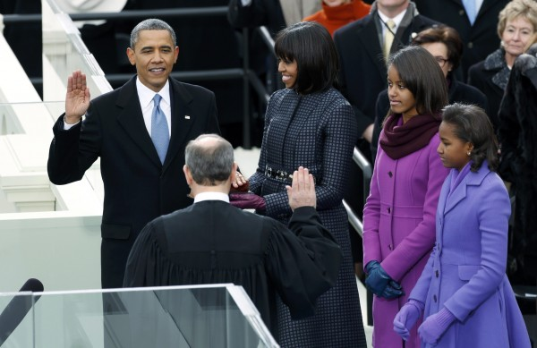 U.S. President Barack Obama is sworn in by Supreme Court Justice John Roberts, as first lady Michelle Obama and the first daughters, Sasha (right) and Malia, look on during inauguration ceremonies in Washington, D.C., on Monday, Jan. 21, 2013.