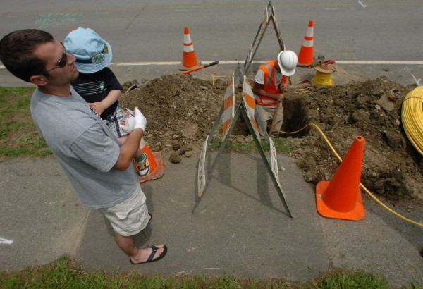 Homeowner Mark Blaine (left) and his son Ethan watch Bangor Gas employee Chris Chambers as he installs natural gas piping under Washington Street in Brewer to connect to Blaine's home in June 2008.