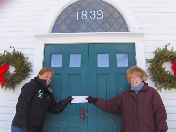 Kimberly Gates of the Bath Area Food Bank accepts a check from the West Bath Historical Society, presented by Avery Meyers, president. The donation represents the shared proceeds from the historical society's annual Christmas service offering.