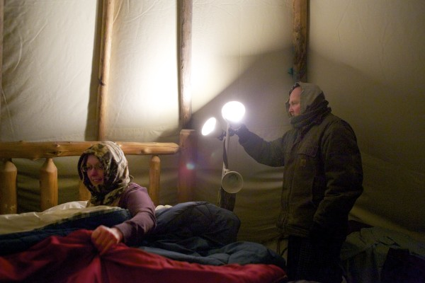 James Winters (right) turns out one of the lights inside his teepee where he and his wife Laura (left) have slept almost every night for the last three and a half years at their Orono home.