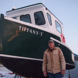 Eliott Thomas stands in front of his lobster boat, Tiffany, at his Yarmouth home on Monday, Jan. 7, 2013. A new regulation requiring commercial fishing boats to be inspected by the U.S. Coast Guard was loosened in the latest Coast Guard Reauthorization Act.