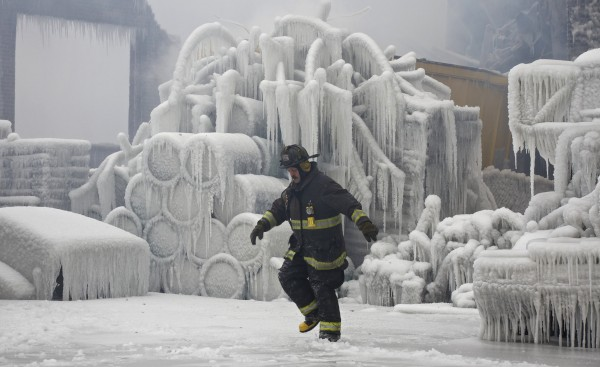 Chicago Fire Department Lt. Charley De Jesus walks around an ice-covered warehouse that caught fire Tuesday night in Chicago on Wednesday, Jan. 23, 2013. Fire department officials said it is the biggest fire the department has had to battle in years and one-third of all Chicago firefighters were on the scene at one point or another trying to put out the flames. An Arctic blast continues to gripped the U.S. Midwest and Northeast on Wednesday, with at least three deaths linked to the frigid weather. Fierce winds made some locations feel as cold as -50 degrees F.