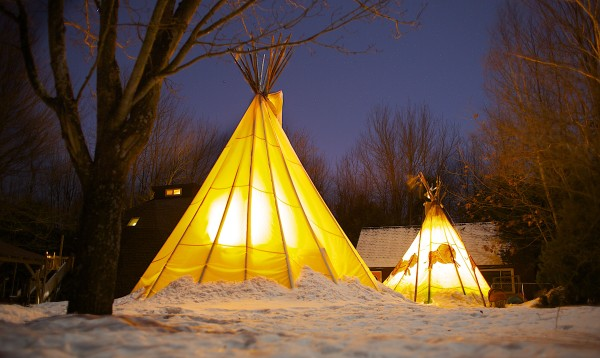 Two of the Winters' three teepees are lit up by lights Wednesday evening, Jan. 23, 2013 at their home in Orono. To reconnect with nature, James and Laura Winters have slept in a teepee almost every night for the last three and a half years, including the winter months.