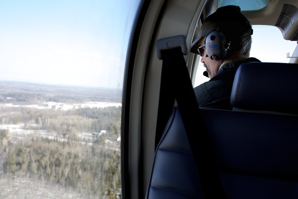 Lee Kantar, a wildlife biologist for the Maine Department of Inland Fisheries and Wildlife, looks through the window of a Bell 407 helicopter while doing a moose survey over Maine's Wildlife Management District 19 on Tuesday morning, Jan. 29, 2013.