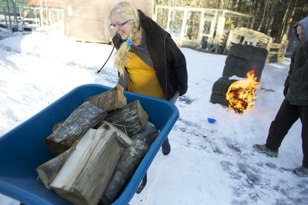 Laura Winters pushes a wheelbarrow full of wood to their teepee that James Winters had started a fire inside on Wednesday, Jan. 23, 2013.