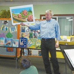 Children's book author Chris Van Dusen holds up one of his books as he speaks to fifth graders at Fisher-Mitchell School in Bath on Monday, Jan. 28, 2013.