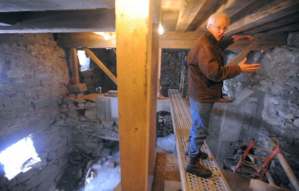 Tony Grassi stands in the basement of the mill at Freedom Falls. This area used to house the original turbines. A modern water turbine will be installed to produce electricity for the building and several homes.