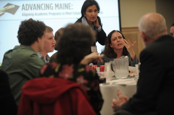 Sarah Hardy (seated), associate professor of mathamatics at the University of Maine-Farmington and Sheena Bunnell (standing), professor of business and economics at UMF and the director of the Maine Health Research Institute, joined colleagues in a roundtable discussion -- part of an April 2010 academic summit at Wells Conference Center at the University of Maine in Orono. The summit drew campus community from the University of Maine System to assess Maine's future workforce needs and academic program development.