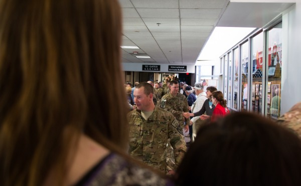 Troops enter the terminal while Kelly Dixon (left) and Christine Bell (right) wait for Pfc. Caleb Frappier to walk off the plane from Afghanistan.