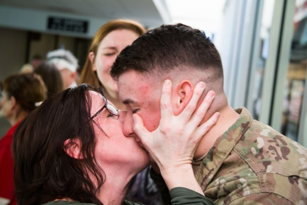 Christine Bell kisses her son Pfc. Caleb Frappier after he returns from his nine-month tour in Afghanistan. Frappier arrived at the Bangor International Airport along with 300 other Army troops on Thursday, Jan. 10, 2013.