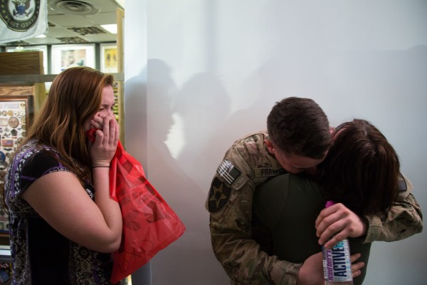 Army Pfc. Caleb Frappier greets his mother, Christine Bell, (right) and his fiance, Kelly Dixon (left), after returning form a nine-month tour of duty in Afghanistan.