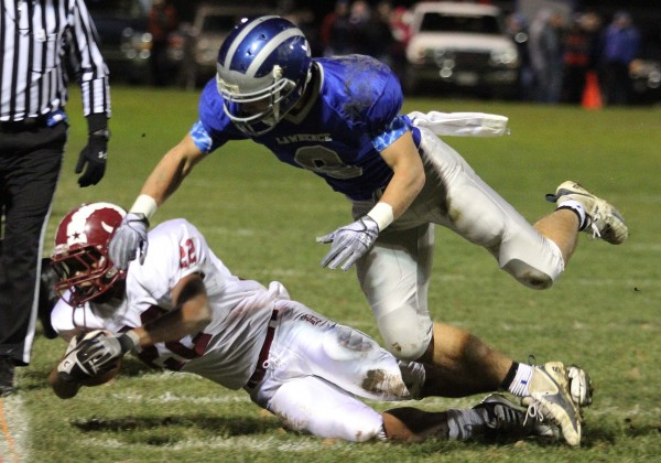 Lawrence's Spencer Carey (right) knocks down Bangor's Xavier Lewis during a game in November 2011 in Fairfield. Carey has committed to play football at the University of Maine next fall.