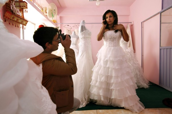 Fereshta Kazemi (right) talks on the phone while trying on wedding gowns for a new film titled, &quotIce Sun.&quot Fereshta will play an Afghan woman married in a traditional village. She suggested that she discard the wedding cloak, and instead bare her shoulders. &quotNo! Cover your shoulders!&quot the movie's producer, Omar Zazai Ramin, told her. &quotDo you want to get us all killed?&quot
