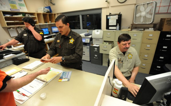 Piscataquis County corrections officers (from left) Ronald Moulton, Joshua McGuire and Alan Wintle staff the booking room at the Piscataquis County Jail in June 2010 during mail and medication call.