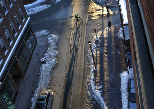 A bicyclists casts a long shadow while riding through downtown Portland on Wednesday, Jan. 2, 2013.