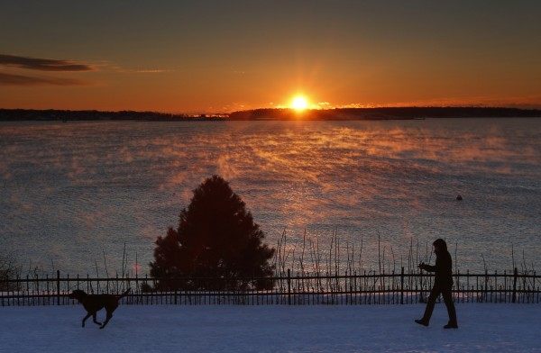 A woman walks her dog on the Eastern Promenade, overlooking Casco Bay in Portland, as sea smoke rises from the water, on Thursday, Jan. 3 2013. The morning temperature was in the low single digits.