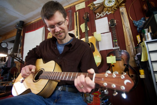 Bath-based luthier Carter Ruff plays a brand new guitar Tuesday Jan. 8, 2013 he made from a pew in his church, which burned down in June 2011. The pine and ash creation was auctioned off to raise money for reconstruction and fetched $3,000.