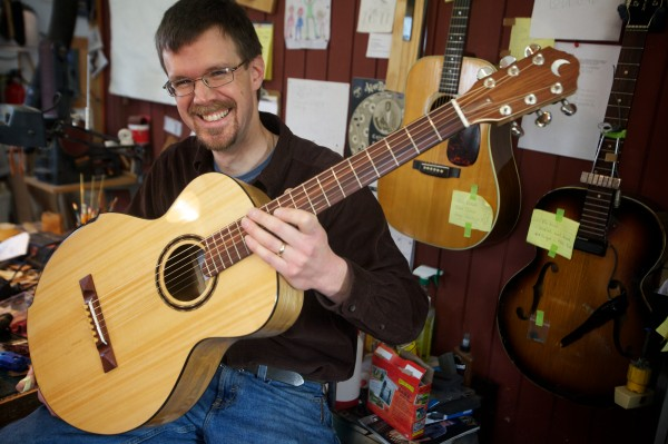 Bath-based luthier Carter Ruff shows off a brand new guitar Tuesday Jan. 8, 2013 he made from a pew in his church, which burned down in June 2011. The pine and ash creation was auctioned off to raise money for reconstruction and fetched $3,000.