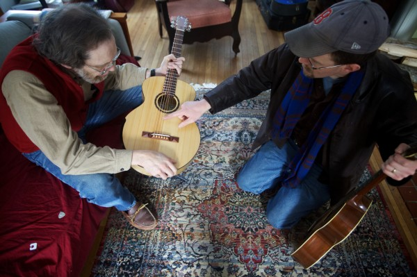 Carter Ruff (right) explains the finer points of the compensated bridge on a guitar he made while delivering it to its new owner, Steve Wellcome on Tuesda,y Jan. 8, 2013.  Ruff made it from a pine and ash pew in the church where Wellcome's wife, Sylvia Stocker, is minister.