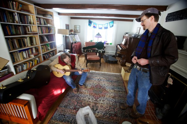 Carter Ruff (right) listens to the guitar he made while delivering it to its new owner, Steve Wellcome on Tuesday Jan. 8, 2013. Ruff made it from a pine and ash pew in the church where Wellcome's wife, Sylvia Stocker, is minister. It burned down in 2011.