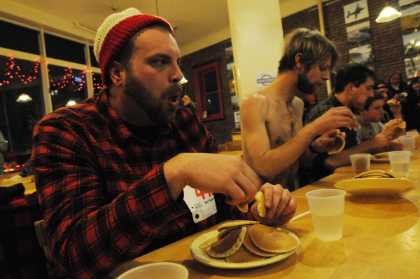 Tim Kenny of Orrington, left, and Adam Goode of Bangor compete in the first annual Paul Bunyan pancake-eating contest at Bagel Central on Monday night. Goode stripped off his shirt in hopes of getting style points from the judges. Dan Bullard won the contest, consuming 11.5 of 15 pancakes in 5 minutes. Nick Lam of Billings won the amateur contest finishing 13.5 pankakes in 5 minutes.