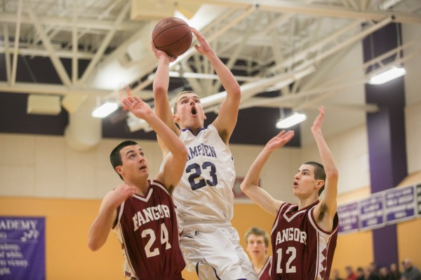 Hampden Academy's Zachary Gilpin (center) splits Bangor defenders Matt Cosgrove (left) and Sean Tocci (right) on Friday, Jan. 18, 2013.
