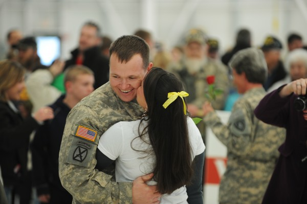 A couple embrace and kiss during a homecoming ceremony at the Army Aviation Support Facility on Hayes Street in Bangor on Friday, Jan. 25, 2013. The Maine Army National Guard