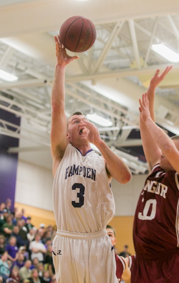 Hampden's Brian Fickett (left) attempts a layup over Bangor's Liam Harrigan (right) on Friday, Jan. 18, 2013.