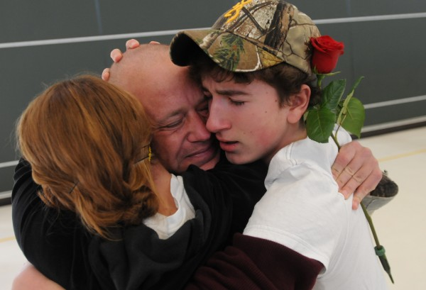 Tears flow as Sgt. Michael Johnson is embraced by his son, Brady (right,) and his daughter, Payton, during a homecoming ceremony at the Army Aviation Support Facility on Hayes Street in Bangor on Friday, Jan. 25, 2013. Jophnson was returning from deployment with the Maine Army National Guard