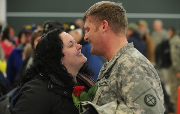Engaged couple Nick Walz and Delena Corey, both of Canada, embrace and kiss during a during a homecoming ceremony at the Army Aviation Support Facility on Hayes Street in Bangor on Friday, Jan. 25, 2013. Walz was returning from deployment with the Maine Army National Guard